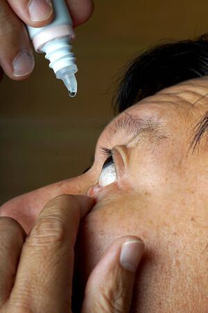 eyedropper: asia man use medicine eyedropper to his eye drop age 40 to 50 year Stock Photo