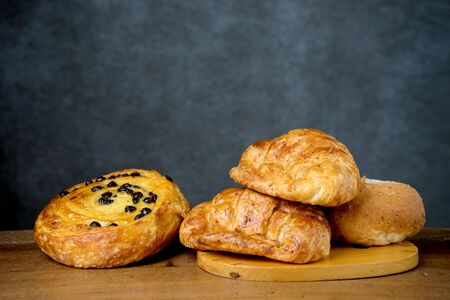 croissant with danish bakery on teak wood table lighting and gray background