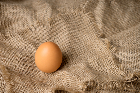 hessian: one egg on burlap material background hessian with frayed edges Stock Photo