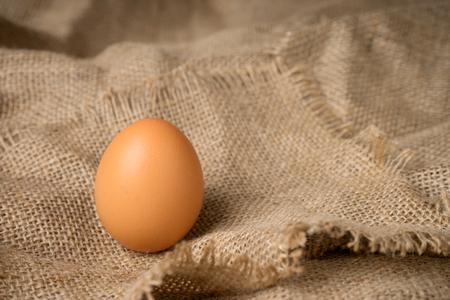 frayed: one egg on burlap material background hessian with frayed edges Stock Photo