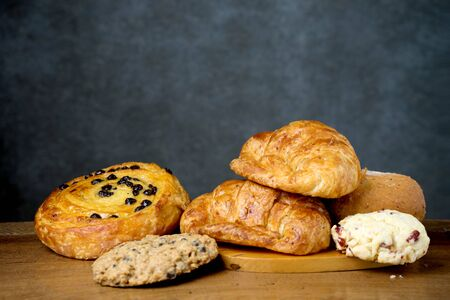 gold teakwood: croissant danish and cookie bakery on teak wood table lighting and gray background