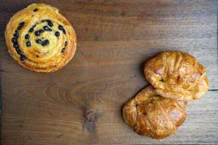 gold teakwood: croissant danish bakery on teak wood table lighting and gray background Stock Photo