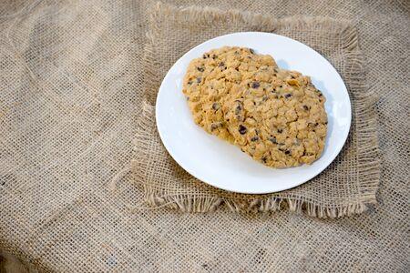 frayed: chocolate chip cookie on white dish burlap hessian with frayed edges Stock Photo