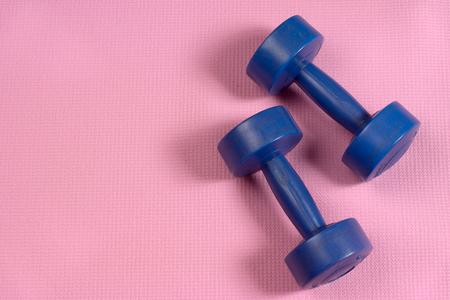 matt: blue dumbells on the pink yoga matt with copy space