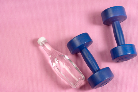 matt: blue dumbells on the pink yoga matt and clear water bottle with copy space