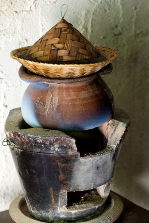 fire place: old  brown clap pot cooking on fire place