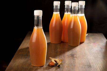 clear bottle: Herbal decoction in clear bottle on wood teak table low key light Stock Photo