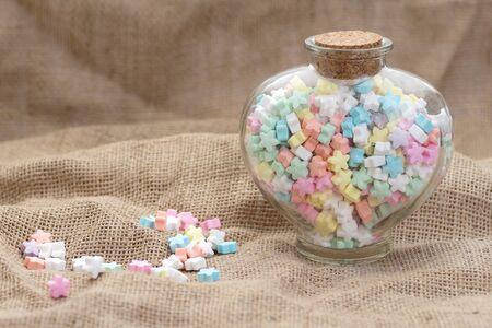 frasco: estrella de caramelo de la forma en el fondo de arpillera textura Corazón de cristal frasco Un montón de espacio de la copia.
