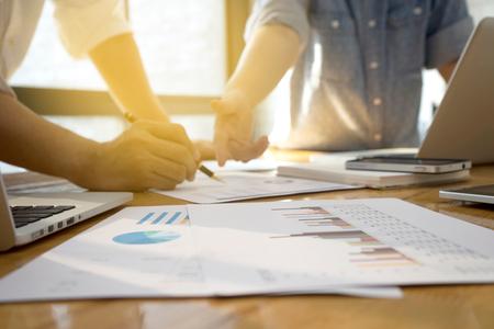 Jóvenes empresas de nuevas empresas metting mujer para hacer el plan de marketing sobre la mesa. con muchos teléfonos libro ordenador papel gráfico del teléfono y la pluma en el tono de la vendimia.