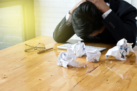 group of bad Paper on table near businessman bend down the head on the table he feel frustrated