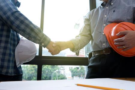 Scossa della mano dell'architetto o dell'architetto nel concetto di lavoro di accordo di successo