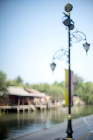 walking pole: Blur river view house on water side opposite to walking way with lamp pole Stock Photo
