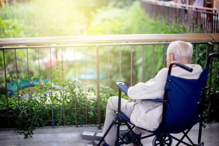 늙은이 휠체어에 앉아 공원에 외로운 보살핌을 기다리는 채우기