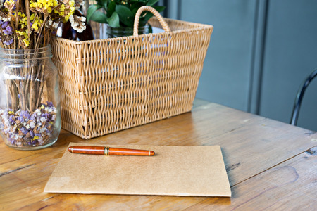 pen on brown note book near rattan basket on wood table.