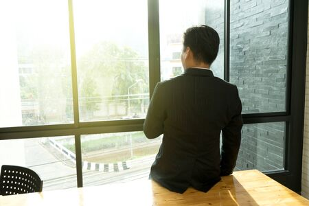 businessman looking out from the window think about business hope and future Stock Photo