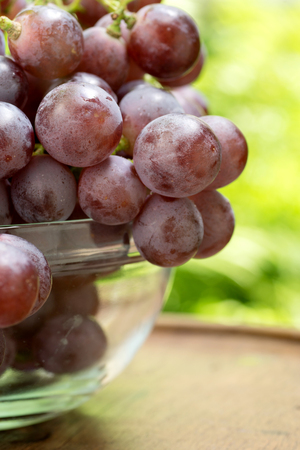 grape seed: red grape seed in grass bowl on wood table with green leaf background