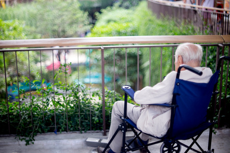 oldage: old man sit on wheelchair looking out to the park fill lonely waiting for take care