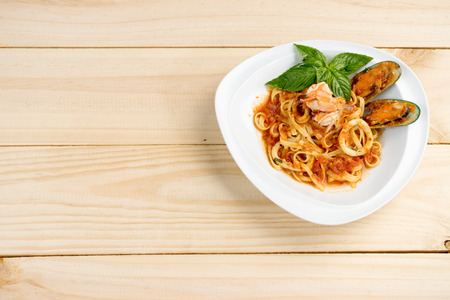 italian sea: italian  sea food pasta wiht shrimp shell in white dish on wood table Stock Photo