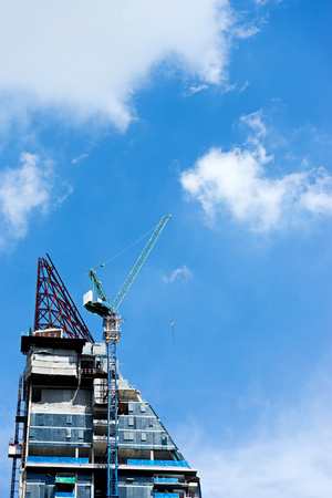 crane working on the top of building with blue sky Stock Photo