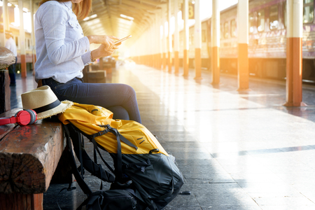 woman with her backpack sitting in train station for start her travel program Imagens