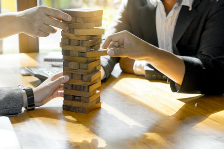 Businessman and Businesswoman group plan and play jenga wooden box wood material game concept for test and prepare risk of marketing plan