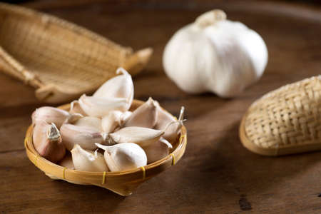 close up shot of garlic on wood background low key studio shot Stock Photo