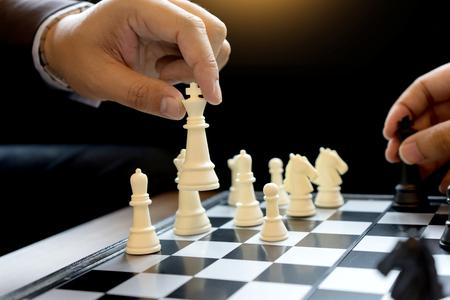 Homme d'affaires jouent aux échecs utilisent King Chess Piece blanc pour écraser le renversement de la stratégie d'entreprise de concept de concurrent pour la victoire