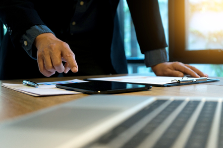businessman boss stand and use tablet and computer for plan company work.