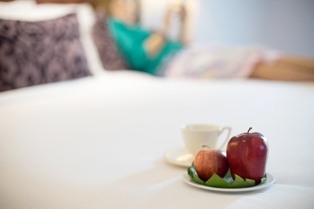 Fruit and coffee on the bed red apple with blur woman relax in the bed room Stock Photo