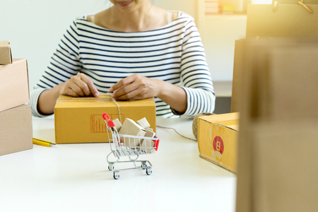 business woman packing for good product to send to customer for the online order 版權商用圖片 - 90471890