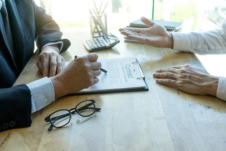 Biznesowy człowiek i prawnik patrząc na umowę biznesową i uczą się podpisywać papier kontraktowy