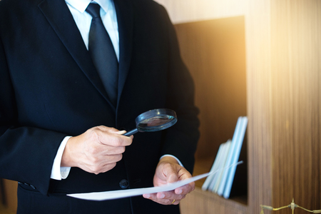Judge lawyer read paper text by use Magnify glass concept law firm