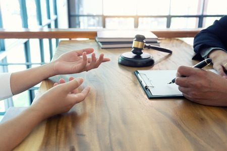 Judge gavel with Justice lawyers having team meeting at law firm in background. Concepts of law or Auction. Stock Photo