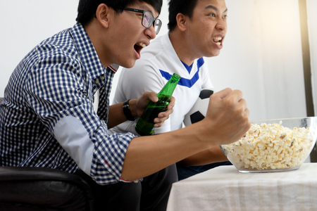 Group of young people man  watch Football match on tv broadcast program  cheer and existing