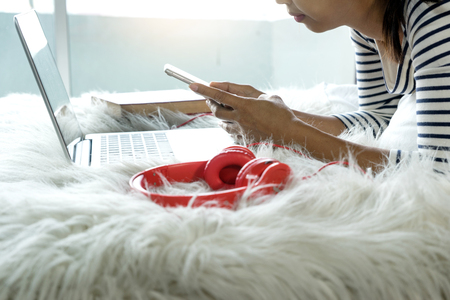 girl lying on the bed play her smartphone and laptop computer with red headphone