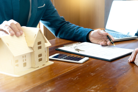 Business man agreement to sign for contract for new home buy or rent , talking and have a home model on the table Imagens