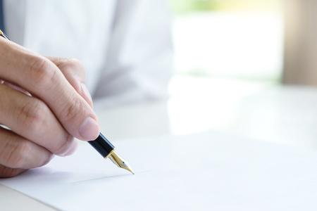 Hand man vrouw op papier met trouwring op papier om huwelijk of echtscheiding te ondertekenen