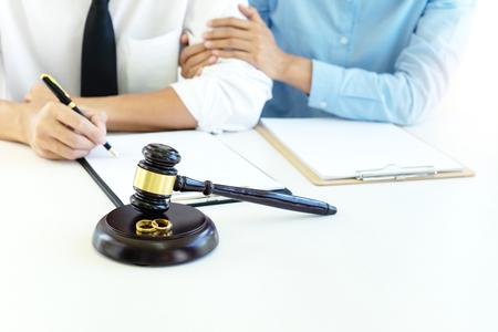 Mann und Frau sitzen romantisch zusammen, um Papier im Anwaltszimmer zu unterschreiben sign