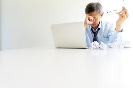 l'homme d'affaires s'assoit à la table remplit de tristesse et de maux de tête, d'échec ou de problème d'entreprise conceptuelle