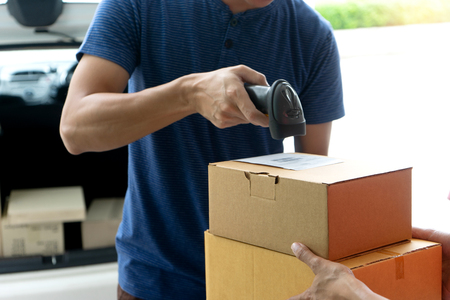 worker man delivery the boxs to woman home or office , use barcode scan reader to get the data for report by computer