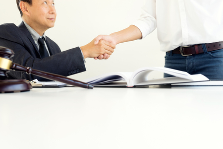 Justice lawyers Handshake to businessman or client for law agreement with Judge gavel. advice and justice law firm concept.