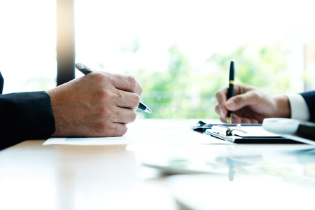 Two businessman hold pen on their hand, for sign paper or business contract agreement on the table.