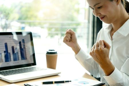 un travailleur indépendant travaille dans le café, sur une table, un ordinateur portable et un graphique en papier marketing avec calculatrice. Elle se sent si heureuse et excitée. Banque d'images