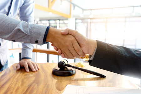 Lawyer or judge  with gavel and balance handshake with client or customer about agreement how to  use arbitration Stok Fotoğraf - 120472534
