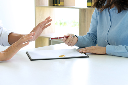 man and woman sit at the table to sign or not on the paper about marry or divorce Stock Photo
