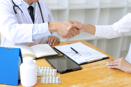 professional doctor handshake to the patient after they have good advice for the good health , on the table there are bottle of medicine.