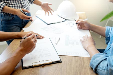 Gruppe von Ingenieuren oder Architekten, die mit Architektenausrüstung, Bauingenieur oder architektonischem Projektkonzept diskutieren und an Blaupausen arbeiten. Standard-Bild