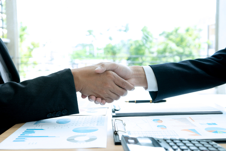 businessman hand shake with another business man  on the table show their working about analysis marketing have graph chart on the table Фото со стока
