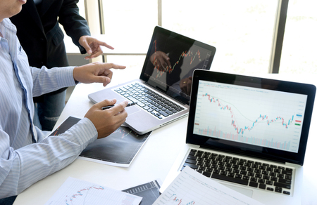 business man and woman sit at ther table looking at computer laptop in the office , they talking about stock market invest or talk with customer