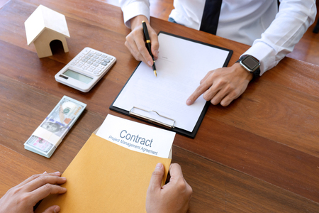 Business man agreement to sign for contract for new home buy or rent , talking and have a home model on the table Stock Photo